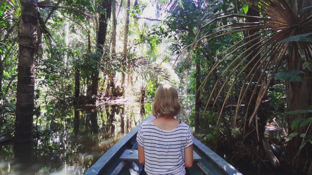 Mujer navegando por lago sandoval en selva peruana